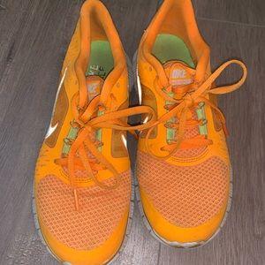 Neon orange nike free sneakers